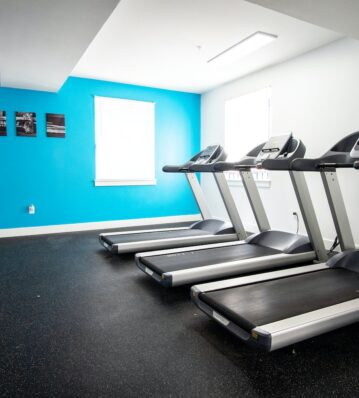 HH Eleanor's gym's treadmill facing cyan and white wall