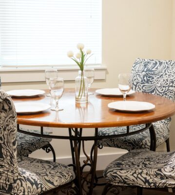 black and white pattern chairs around a brown set table next to a closed window